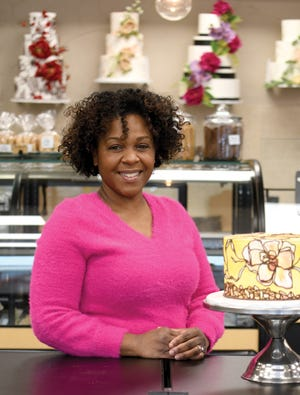 Studio Bakery co-owner Kara Hammett poses with a cake in the bakery.