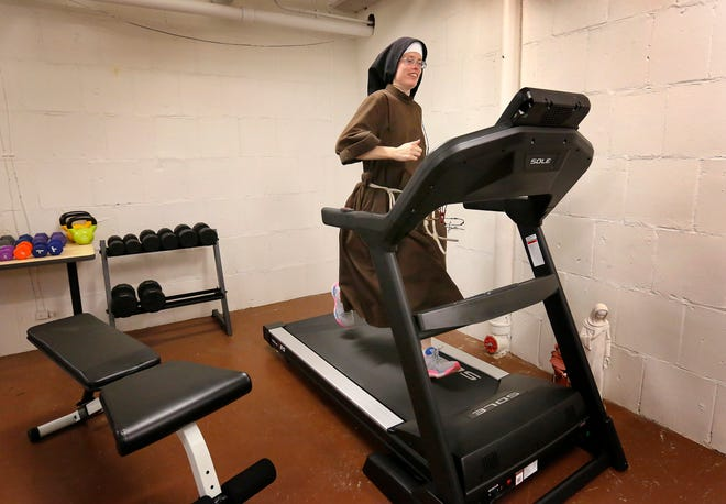 Franciscan Sister of the Eucharist Stephanie Baliga, a former star runner at Auburn High School and at the University of Illinois, runs on a treadmill in the basement of her community's convent on Aug. 15, 2020 in Chicago. On Aug. 23, Sister Stephanie ran a marathon on the treadmill to raise money for the Mission of Our Lady of the Angels.