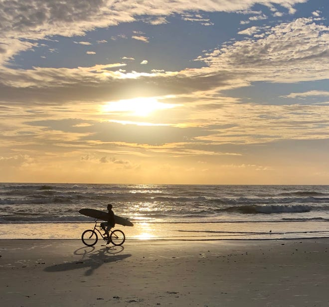 Surfer bikes his way to the best waves at St. Augustine Beach.