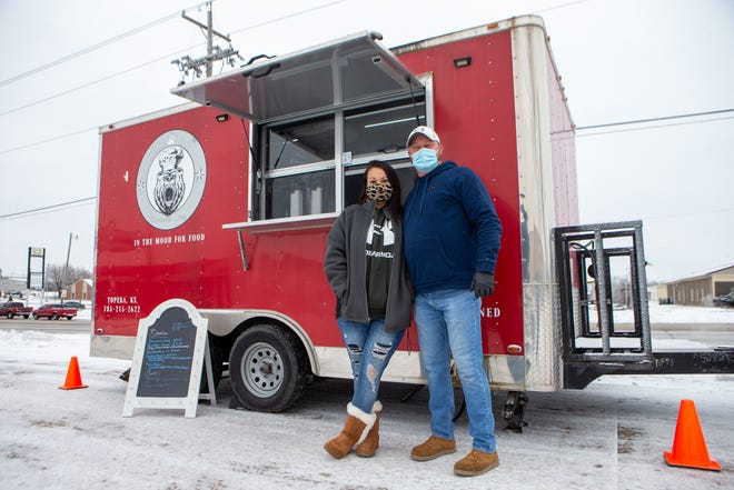 Ashley and Eugene Behrens, owners of Behr Paws Southern Oven, stand Tuesday morning outside their food truck in front of the Helping Hands Humane Society.
