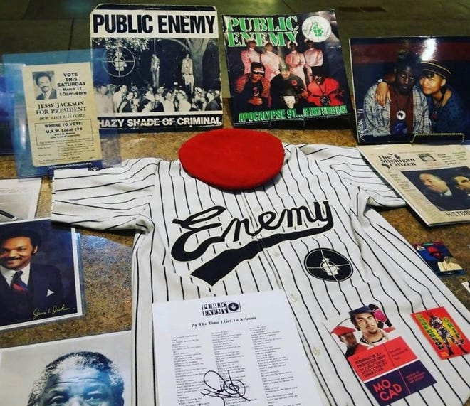 Memorabilia for Public Enemy, an American hip-hop group formed in 1985, is displayed on a table. The items are part of the Black History 101 Mobile Museum collection.