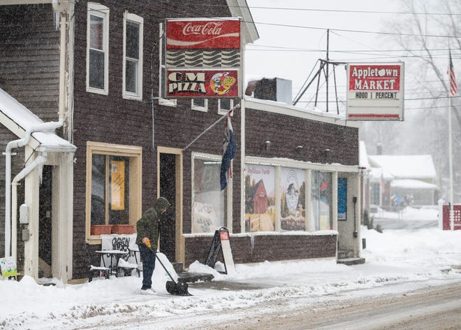 A man clears the sidewalk in front of C&M Pizza in the center of Sterling during the storm on Tuesday.