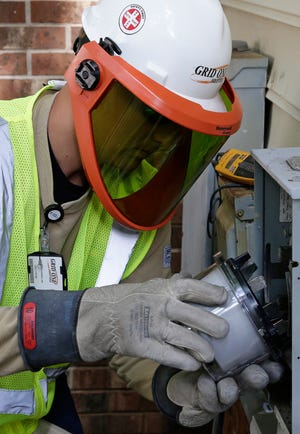 A workers installs a smart meter at a residence in Raleigh, N.C.