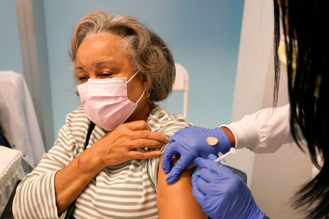 A 74-year-old woman receives the Pfizer-BioNTech COVID-19 vaccine at a hospital in Miami.