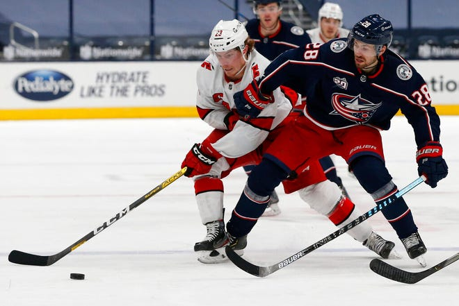 Carolina Hurricanes' Brock McGinn, left, and Columbus Blue Jackets' Oliver Bjorkstrand chase a loose puck during the second period of an NHL hockey game Monday, Feb. 8, 2021, in Columbus, Ohio. (AP Photo/Jay LaPrete)
