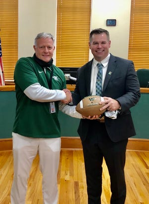 Waxahachie AD Greg Reed presented new head football coach Shane Tolleson with a custom football following Monday's hire.