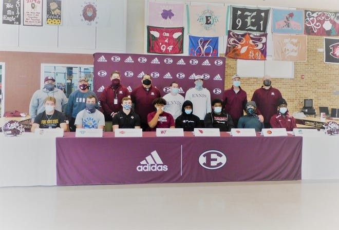 Backed by their coaches, Ennis football players get seated for their signing day activities at Ennis High School last Wednesday.