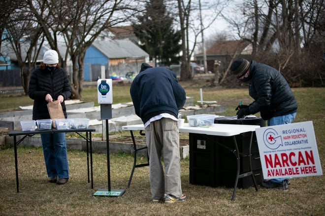 (Right) Daryl Hams, a registered nurse and a project director of the Regional Harm Reduction Collaborative, fills out paperwork for a client at a makeshift outdoor booth in Hamilton, while Jennifer Williams also helps.