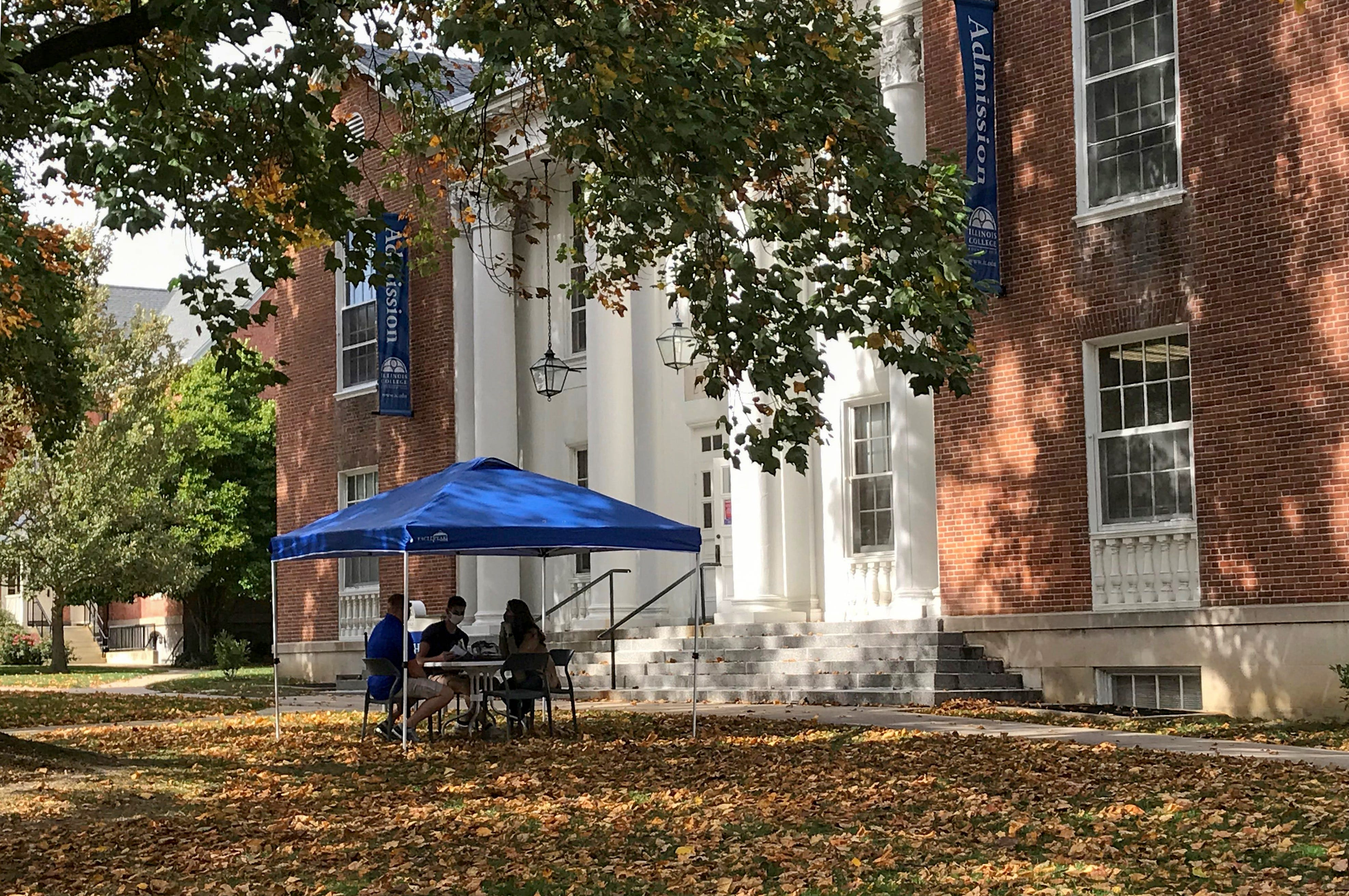 Potential students meet with an admissions counselor on a sunny early fall day on the campus of Illinois College