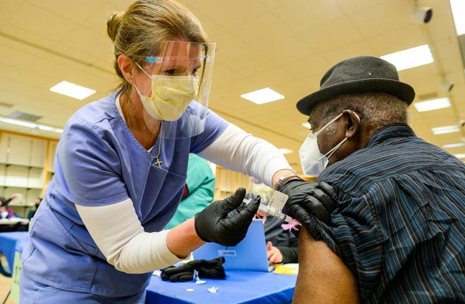 Susan Geubtner, a nurse with Montana Veterans Affairs, gives a COVID-19 vaccination to Robert Harris a veteran of the U.S. Air Force on Tuesday morning during a vaccination clinic for veterans at the Holiday Village Mall.