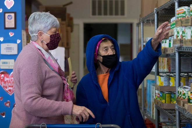 Henderson Christian Community Outreach executive director Mary Dunham, left, assists Minnie Taylor as she picks out groceries Wednesday morning, Feb. 9, 2021.