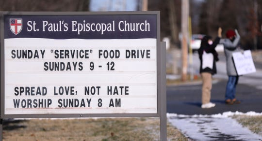 St. Paul's Episcopal Church members wave at passing traffic while displaying signs seeking food and essential goods donations in Louisville, Ky., on Feb. 7. The church will deliver the donations to the food pantry at the Calvary Episcopal Church downtown.