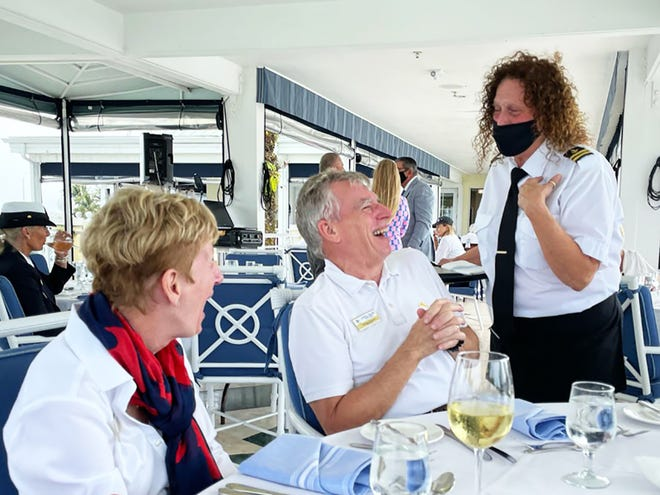 Ellie and Dave Everitt share a laugh with bartender Kathy Tummarello at the blessing of the fleet luncheon.