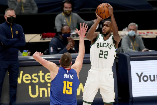 Khris Middleton shoots over Nikola Jokic on Monday night. Middleton scored 29 points and had 12 assists in the Bucks' victory.