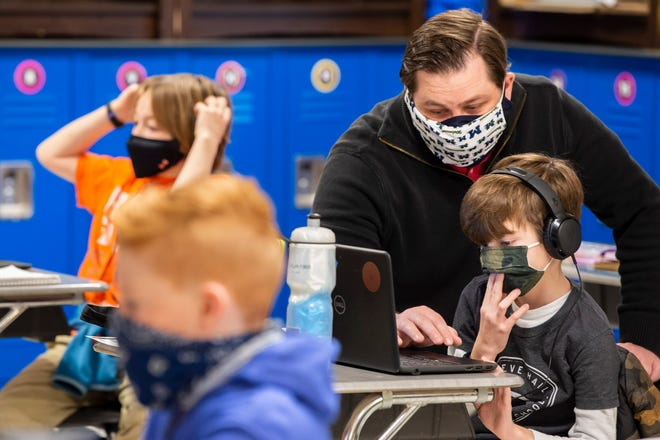 Fourth Grade Teacher Kenneth Knight assists students in connecting to the internet on the first day back to in-person learning at Crieve Hall Elementary School on Tuesday, Feb. 9, 2021 in Nashville, Tenn.