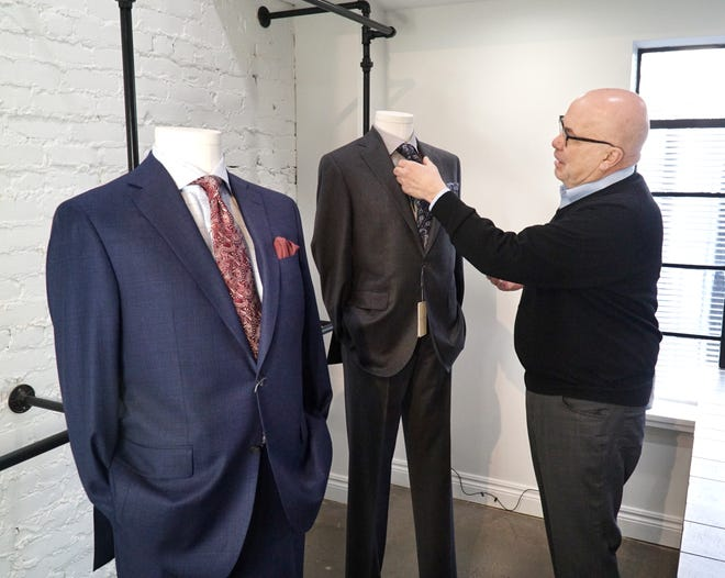 Craig Ryan clothier general manager Keith Saltsman adjusts a suit from the Jack Victor line at the Birmingham shop on Feb. 9, 2021.