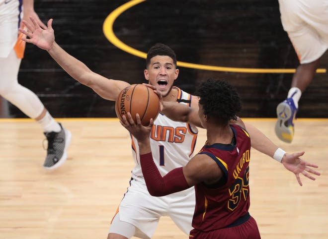 Phoenix Suns guard Devin Booker (1) pressures Cavaliers guard Isaac Okoro (35) during the Suns' 119-113 win Monday night in Phoenix. [Michael Chow/Arizona Republic]