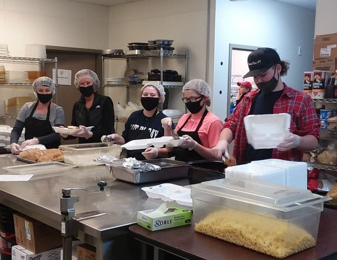 Volunteers from the St. John's Lutheran Church in Oak Harbor help Bistro 163 prepare meals for the free community dinner offered on Monday.