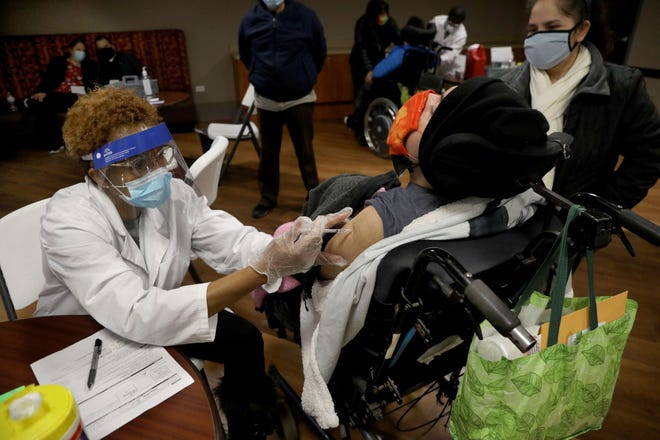 Walgreens pharmacist Connie Fogg gives a COVID-19 vaccine to Evaristo Maldonado during an inoculation clinic for more than 800, including over 400 with intellectual and developmental disabilities, at Seguin Services on Feb. 4, 2021, in Cicero, Illinois. (Antonio Perez/Chicago Tribune/TNS)