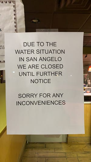 A sign on a storefront announces its closure due to a 'do not use' water advisory issued Monday, Feb. 8, 2021.