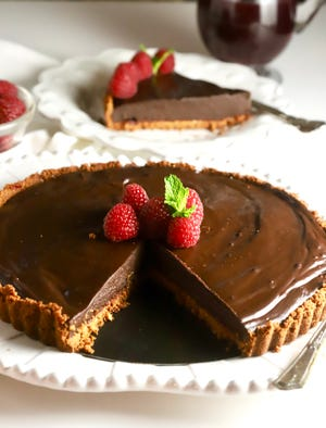 Chocolate ganache tart is made with semi-sweet adnd bittersweet chocolate and topped with raspberries.