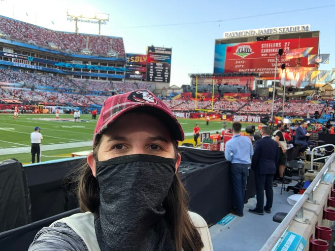 """Sporting a plaid Florida State University baseball cap, something she is known for, Tallahassee freelance photographer Melina Myers takes a selfie from her spot in the """"operational zone"""" at Raymond James Stadium during Super Bowl LV Sunday, Feb. 7, 2021."""