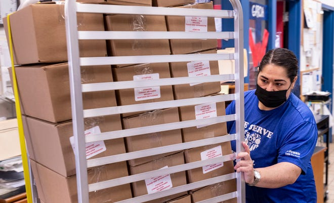Food Services worker Elizabeth Vieira carts 37 meal boxes out for delivery at Tulare Western High School on Tuesday, February 9, 2021. Each box contains seven breakfasts and seven lunches for one student.