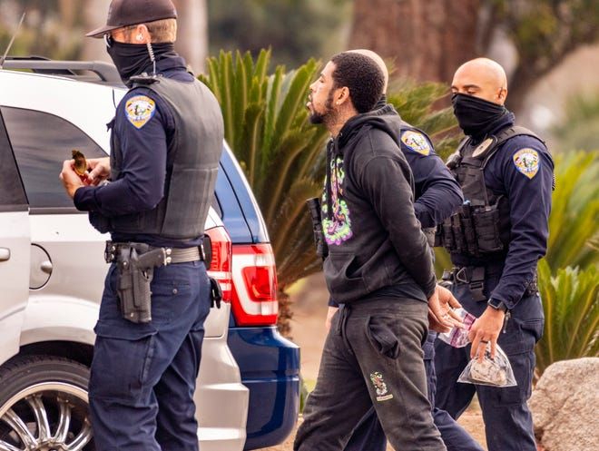 Visalia Police take a man into custody near Walnut Avenue and Divisadero Street on Tuesday, February 9, 2021. The man is a suspect in a homicide late last year. The department's SEU, drone and K-9 units were involved when the man fled. He was later found and arrested without incident.
