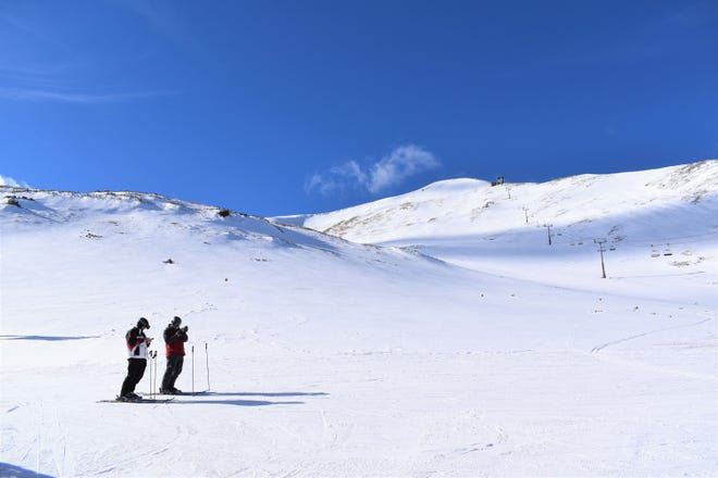 Two skiers check their phones at 12,000 under the peak at Breckenridge on Feb. 2, 2020.