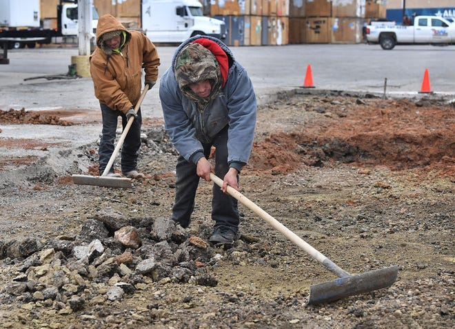 Martin Macias, left, and Marco Maldonado of Duke Construction Company, do ground work for a parking lot repair at A-1 Freeman Moving Tuesday morning, Both workers wore three coats to deal with the bitter cold and wind.