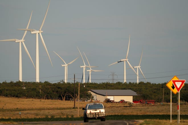 A vehicle drives past wind turbines on a rural road near Sweetwater, Texas, in this July 29, 2020, file photo.