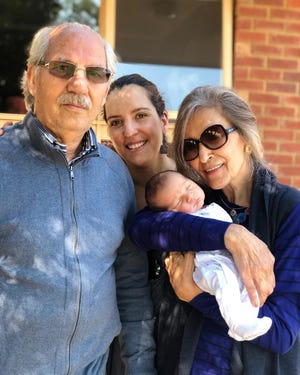 Sarvin Haghighi, center, with her parents in Melbourne shortly after son Kian was born there in March 2019. Haghighi's parents, both Iranian citizens, have been unable to visit her in the U.S. because of a travel ban imposed by former President Trump in 2017. President Biden lifted the ban on his first day in office.