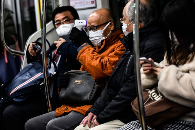 An elderly man checks his body temperature with a non-contact infrared thermometer while commuting on a train in Tokyo on Feb. 9, 2021.