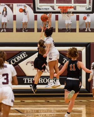 Round Rock's Bailey Featherstone picks up a key block against Westwood's Emma Goolsbey late in the game. Round Rock won a district girls basketball game at home over Westwood 57-54 on Feb. 9.