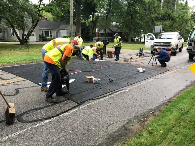 Akron city workers install a speed table in the summer of 2020 on Schocalog Road, one of two locations used to pilot the portable speed-reduction tool that acts like a more gentle speed bump.