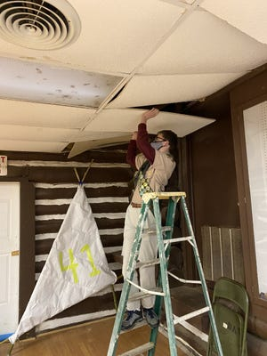 Jaxon Perreault, 16, replaces a ceiling tile at the Hut.