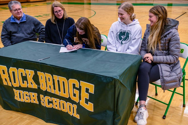 Rock Bridge senior Cassie Gray signs her letter of intent to play volleyball at Webster University as her parents and teammates look on Tuesday night at Rock Bridge High School.