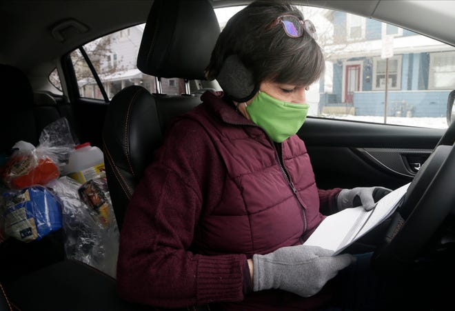 Volunteer Liz Alcalde of Clintonville looks over her run sheet on Feb. 10 as she delivers pet food and supplies as part of LifeCare Alliance's Senior PetCare program.