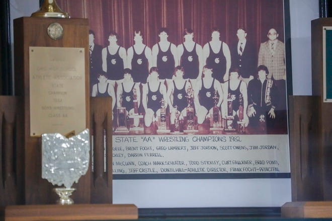 A faded photo of U.S. Rep. Jim Jordan, front row third from right, can be seen with members of the 1982 wrestling state championship in the trophy case at St. Paris Graham High School on Sunday, Feb. 7, 2021. Both Jim and his brother Jeff Jordan each won four state individual wrestling titles when they were in high school at Graham.
