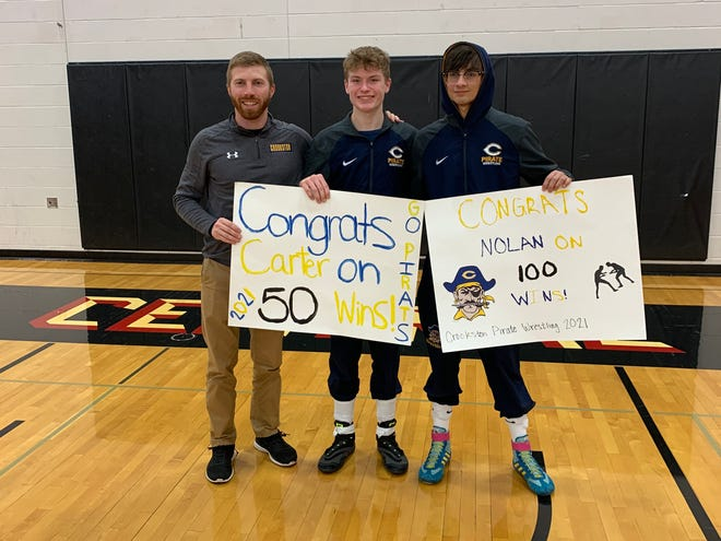 Crookston coach Wes Hanson (left), Carter Coauette (center) and Nolan Dans (right) pose for a picture after Coauette won his 50th career match and Dans won his 100th in Tuesday night's triangular.