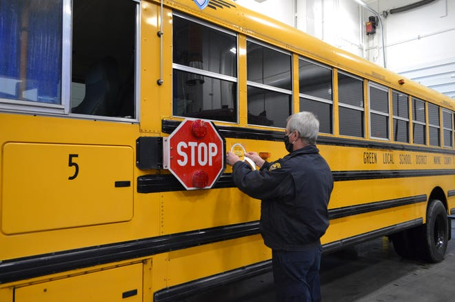 State Highway Patrol inspector Marv Jose places a new annual inspection sticker ona bus in the newly renovated Diesel Technology lab at the Wayne County Schools Career Center.
