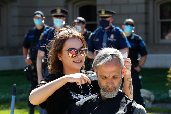 A hairstylist gives a man a free haircut at the State Capitol during a rally as the Michigan State Police watch in Lansing, Wednesday, May 20, 2020. A judge dismissed disorderly conduct charges Monday against six hair stylists who were ticketed last spring during a protest at the Michigan Capitol. The women were cutting hair to protest Gov. Gretchen Whitmer's decision to keep barbershops and salons closed for nearly three months because of the coronavirus pandemic. [AP Photo/Paul Sancya, File]