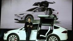 Tesla CEO Elon Musk next to a Model X electric sport utility vehicle during a presentation in California in 2015.