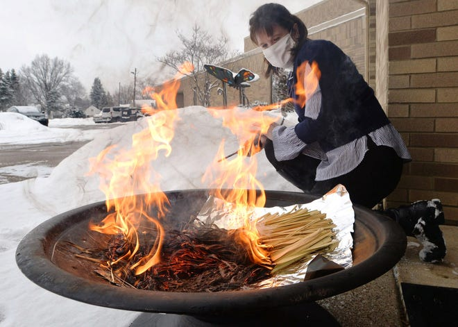 The Rev. Sami Pfalzgraf burns palm fronds to create the ashes to be used in Ash Wednesday services at St. Paul's Lutheran Church on Feb. 9, 2021, in Millcreek Township. Due to the COVID-19 pandemic, she is bagging up small amounts of ash and handing them out so people can observe Ash Wednesday safely in small groups.