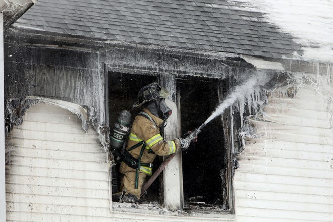 Burlington firefighter Brett Rudy sprays foam Wednesday as Burlington and West Burlington firefighters respond to an apartment fire at 217 S. Woodlawn Ave. The Burlington Fire Department was notified of the fire shortly before 10:30 a.m. when a tenant reported smoke detectors in the building had been activated and that smoke was visible within.