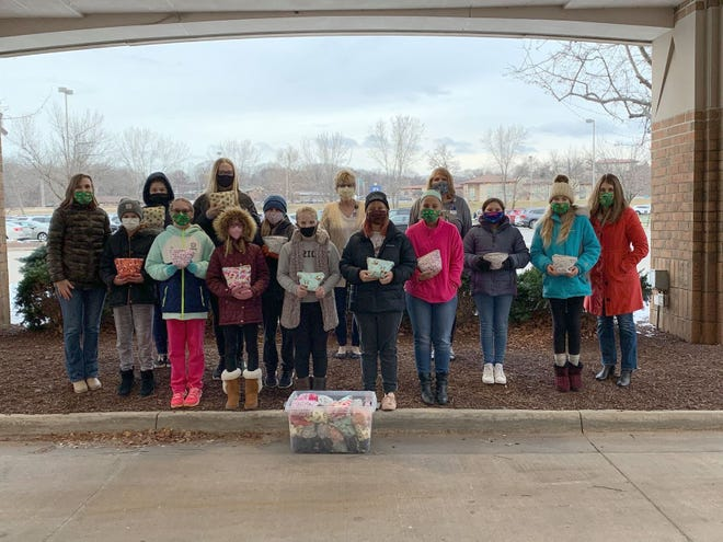 Orion Junior Girl Scouts deliver care bags to patients at the Trinity Cancer Center, Moline. The girls received the Bronze Award for their efforts.