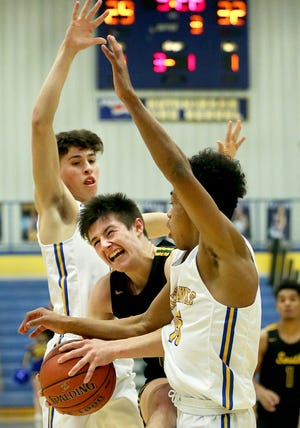 Salina South's Devon Junghans (10) tries to squeeze between Hutchinson defenders Maddix Heneha (5) and Dauntay King (15) during their game Tuesday night at the Salthawk Activity Center in Hutchinson. South edged Hutch, 64-60, to remain undefeated.