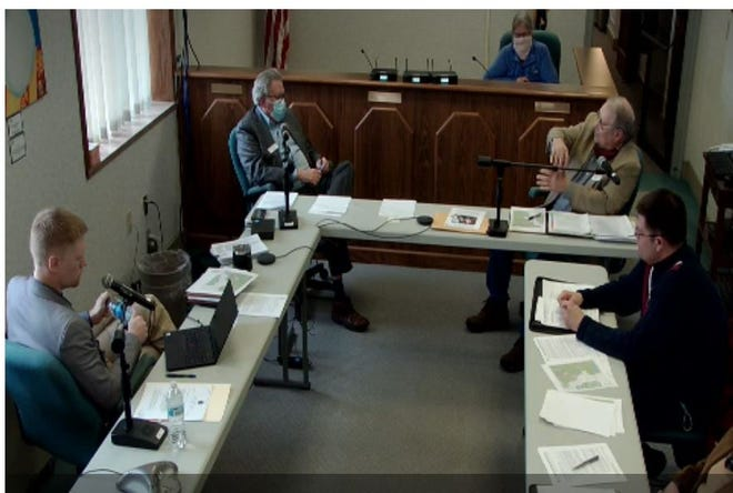 County Commission Chairman Ron Hirst, top right, discusses turbulence created by commercial wind towers as the commission debates setbacks near airports. The commission was meeting about proposed wind regulations Tuesday afternoon. Commissioner Ron Sellers, top left, Commissioner Daniel Friesen, bottom left, and County Planner Mark Vonachen listen.