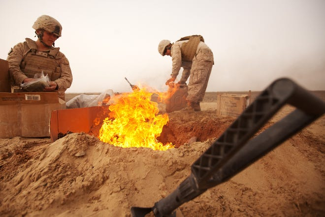 U.S. Marines with 1st Light Armored Reconnaissance Battalion dispose of trash in a burn pit while deployed in Afghanistan, March 2012.