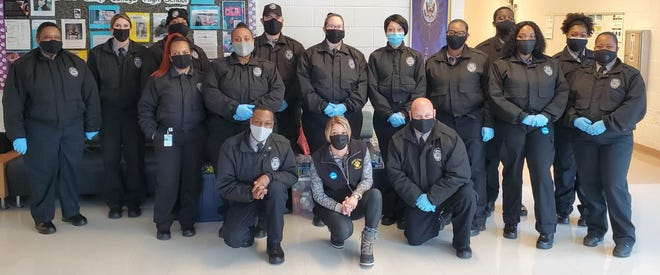 Taiquan Uzzell, on left, kneeling, is pictured with the Department of Public Safety at Lenoir Community College. [CONTRIBUTED PHOTO]